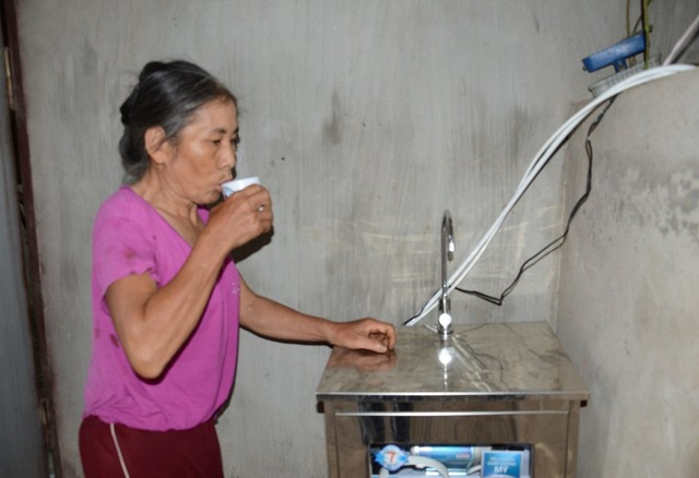 Cô Chiến vui mừng uống nước bên chiếc máy lọc nước được tặng
